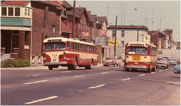 1950s era maroon and cream Hamilton Street Railway trolley buses crossing West Ave on King. St John steeple is at upper right.