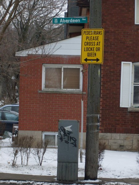 Sign at Aberdeen Ave. and Kent St: 'Pedestrians Please Cross at Locke or Queen'