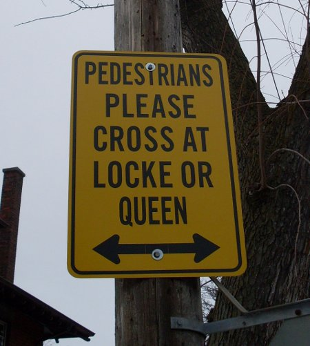 Former sign at Aberdeen and Kent: 'PEDESTRIANS PLEASE CROSS AT LOCKE OR QUEEN'