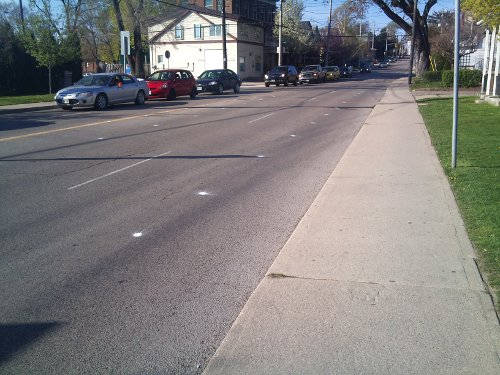 Paint spots on Dundurn Street North mark the location of the upcoming bike lanes (Image Credit: Joey Coleman)