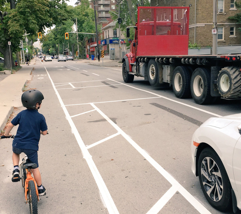A child rides in the protected bike lane on Herkimer while a transport truck drives past (Image Credit: Tom Flood)