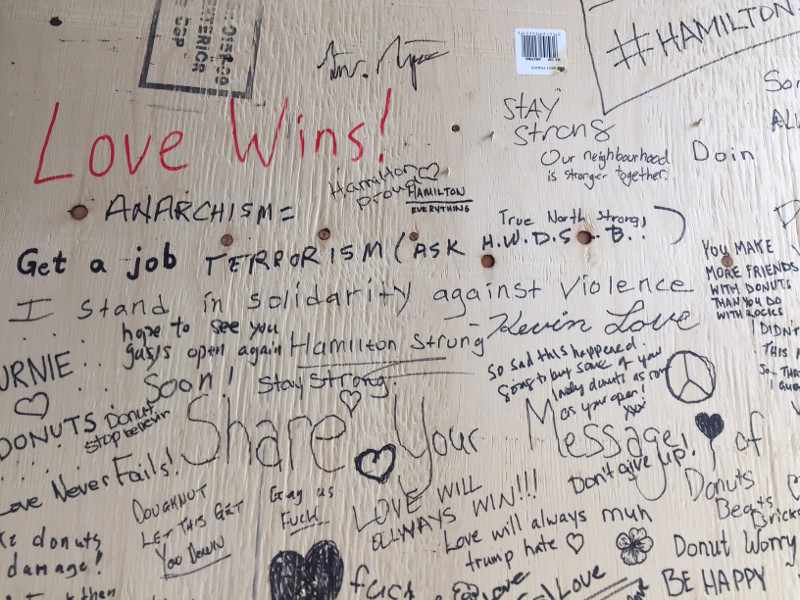 Messages of support on the plywood window covering at Donut Monster