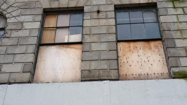 Broken windows covered with plywood
