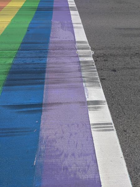 More detail of rainbow crosswalk faded and covered in skid marks (Image Credit: Cameron Kroetsch)