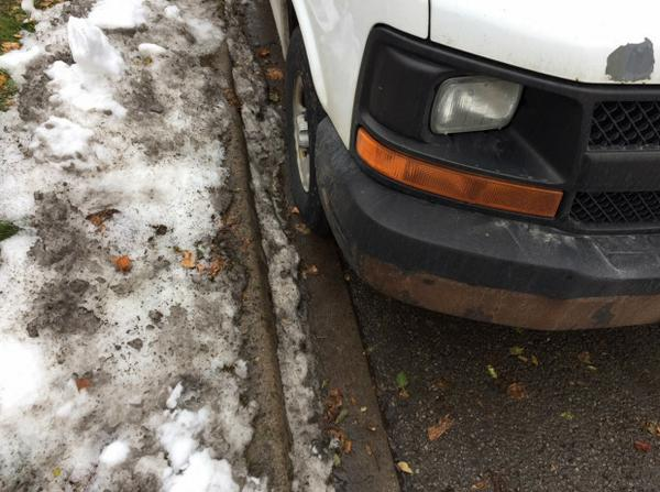 Photo #2: Close up of right front tire of white van in foreground of photo #1