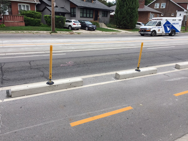 Bicycle lanes protected by concrete curb with knockdown sticks on top
