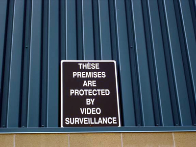 Sign: THESE PREMISES ARE PROTECTED BY VIDEO SURVEILLANCE