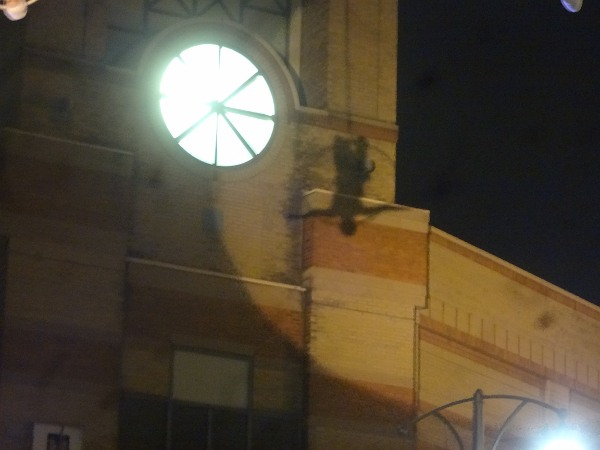 The silhouette of an acrobat is cast against the City Centre clock tower